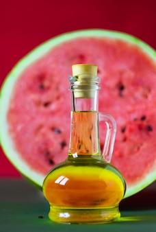 Watermeloen zaden olie in een kleine glazen pot en grote rauwe watermeloen op rode en groene achtergrond