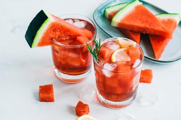 Watermeloencocktail in een glas met citroen en ijsblokjes op tafel. verfrissend drankje