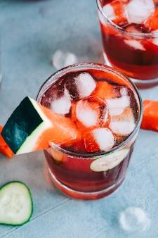 Watermeloencocktail in een glas met schijfje komkommer en ijsblokjes op tafel. verfrissend drankje