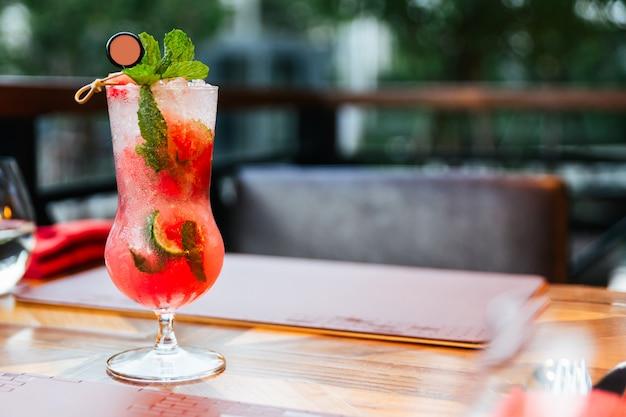 Watermeloencocktail met kaffir-kalk wordt gemengd in het drinken van glas met ijs op houten lijst met exemplaarruimte die wordt gediend.