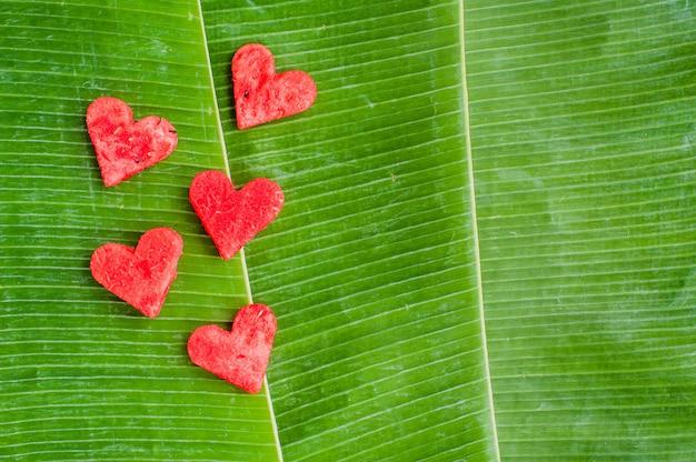 Watermeloenharten op de achtergrond van banaanbladeren. plat liggen