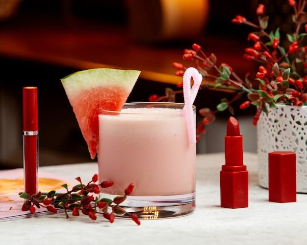 Watermeloenmilkshake gegarneerd met watermeloen, naast rode lippenstift