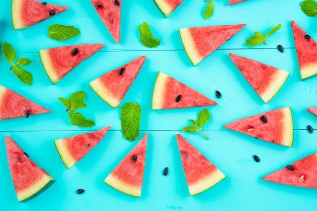Watermeloenplak met muntbladeren op blauwe lijst