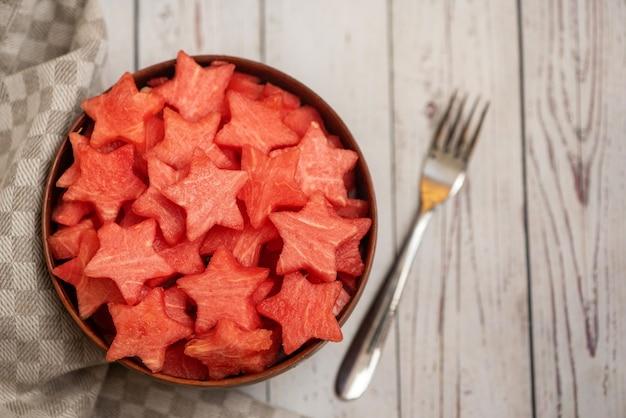 Watermeloenplakken in de vorm van een ster in kom op een licht hout. bovenaanzicht,