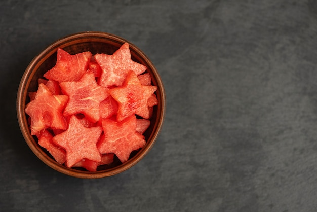 Watermeloenplakken in de vorm van een ster in kom op een zwarte plaat. bovenaanzicht,