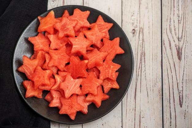 Watermeloenplakken in de vorm van een ster in plaat op een lichte houten achtergrond. bovenaanzicht, met kopie ruimte