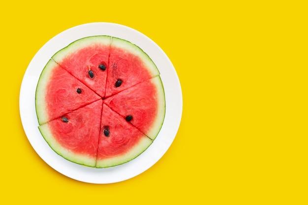 Watermeloenplakken in witte plaat op gele achtergrond.