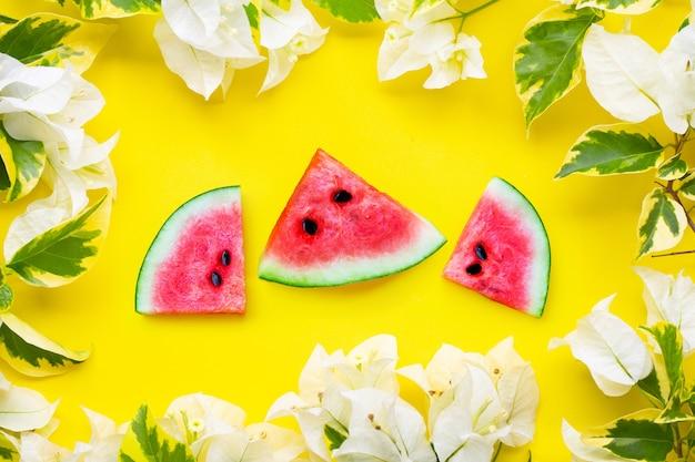 Watermeloenplakken met witte bougainvilleabloemen op geel oppervlak