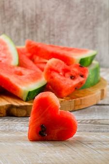 Watermeloenplakken op een scherp raads zijaanzicht over houten en grunge achtergrond