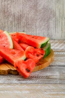 Watermeloenplakken op een scherpe raad op houten en grunge achtergrond. zijaanzicht.