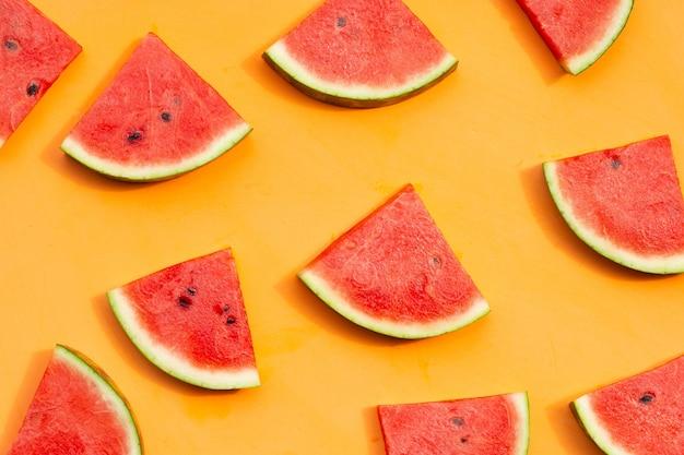 Watermeloenplakken op oranje achtergrond.