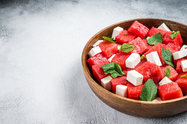 Watermeloensalade met fetakaas in een houten bord. witte achtergrond. bovenaanzicht. ruimte kopiëren.
