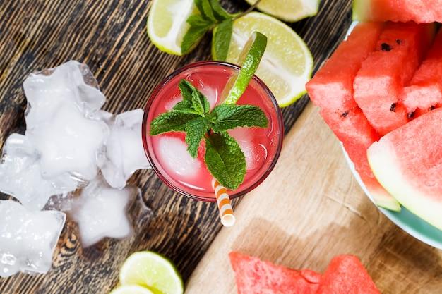 Watermeloensap van rijpe rode en sappige watermeloenen en stukjes ijs, rood sap is een natuurlijk gezond en dieetproduct, watermeloensap wordt in een glazen container met ijs gegoten