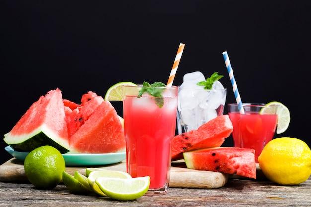 Watermeloensap van rijpe rode en sappige watermeloenen, rood sap is een natuurlijk gezond en dieetproduct, watermeloensap wordt in een glazen container gegoten