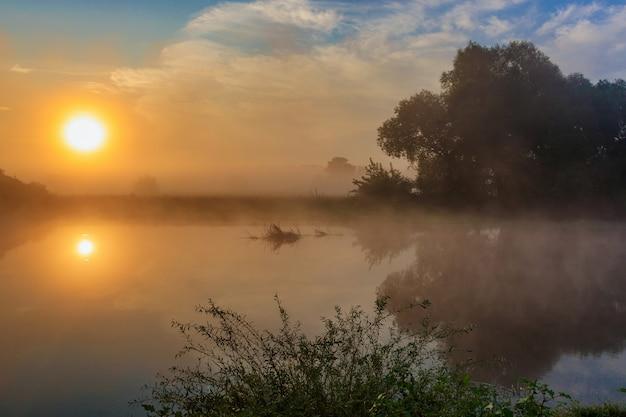 Wateroppervlak van de rivier bij zonsopgang met weerspiegeling van de oranje zon