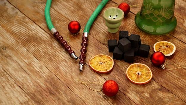 Waterpijp, houtskool, droge stukjes sinaasappel en rode kerstballen op een houten tafel