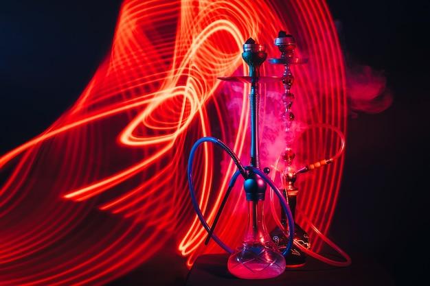 Waterpijpen met hete shisha-houtskool met rode en blauwe neonverlichting op een donkere achtergrond