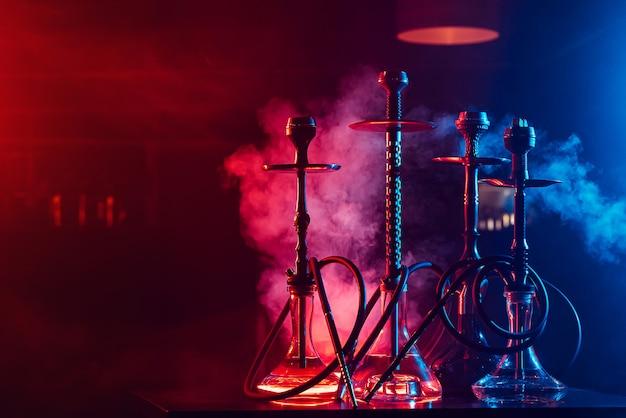 Waterpijpen met shisha-kolen in kommen tegen een achtergrond van rook met neonverlichting in een restaurant met een exemplaarruimte