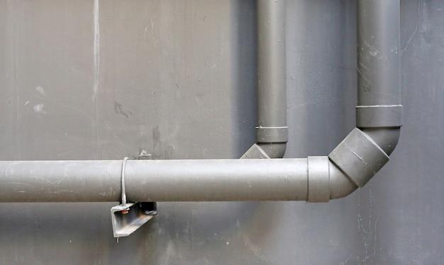 Waterpvc-pijpen op cementmuur van de bouw
