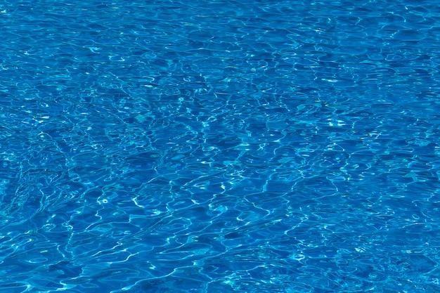 Waterrimpelingen op blauw-betegelde zwembadachtergrond