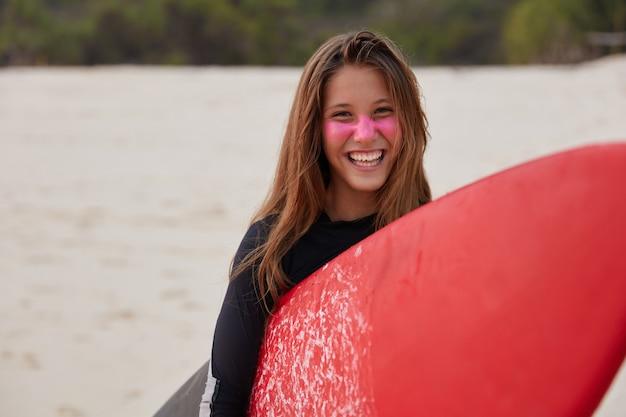 Watersport concept. gelukkig opgetogen surfboarder in duikpak