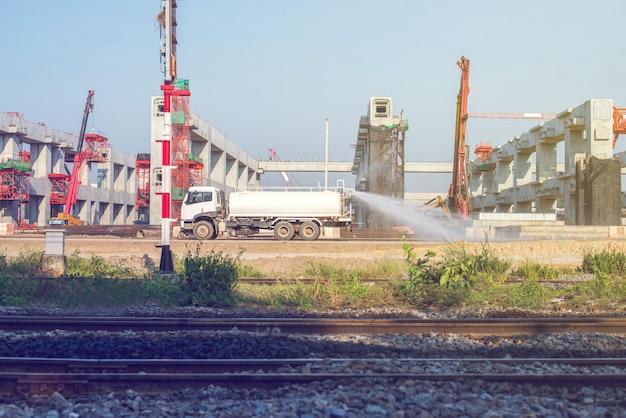 Watersproei-voertuigen in bouwwerkzaamheden om stof op de bouwplaats te onderdrukken