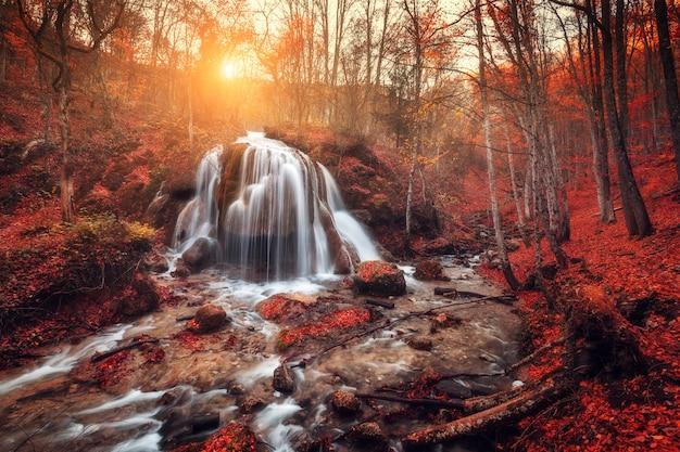 Waterval bij bergrivier in de herfstbos bij zonsondergang