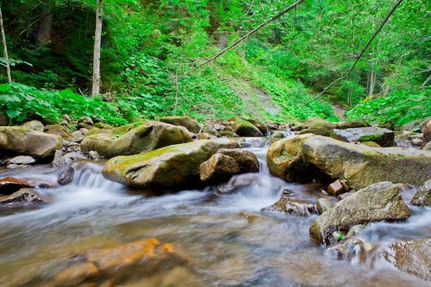 Waterval in het bergbos. mooie achtergrond van steen, water, mos.