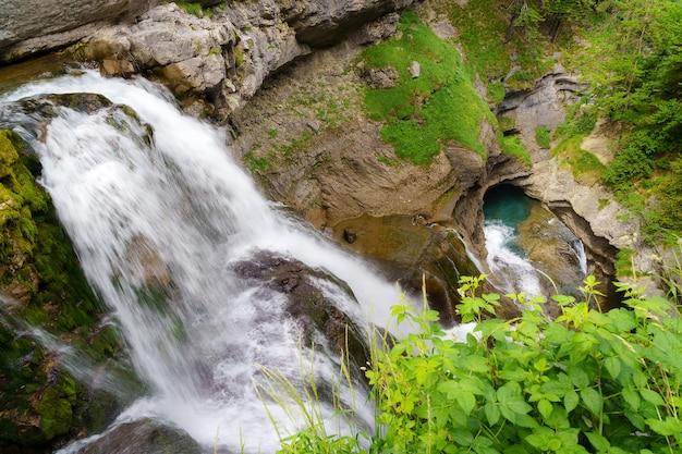 Waterval in twee valt door de rots in zonnig landschap in de pyreneeën van ordesa.