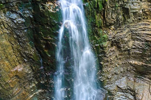 Waterval op de bergrivier met wit schuimend water dat uit rotsformaties in het zomerbos valt.