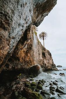 Waterval over rotslandschap en palmbomen