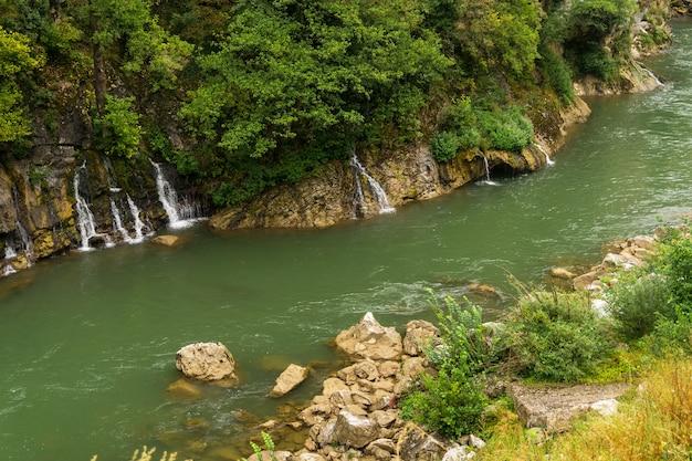 Watervallen op een bergrivier met groen water en rotsachtige kusten