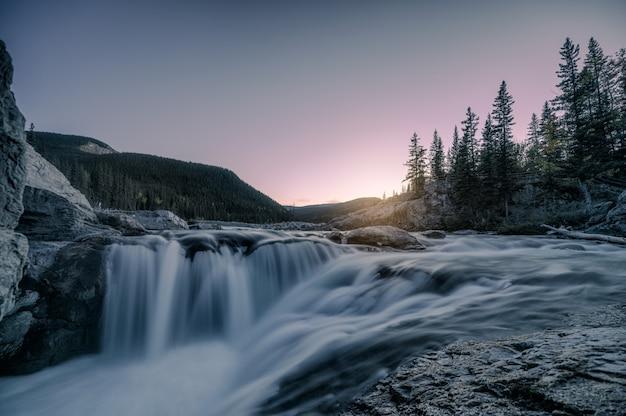 Watervalstroomversnelling die op rotsen in bos op avond stromen