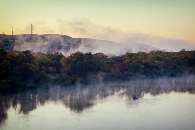 Waterverdamping op de rivier bij dageraad en eenzame visser op een boot bij de herfstseizoen