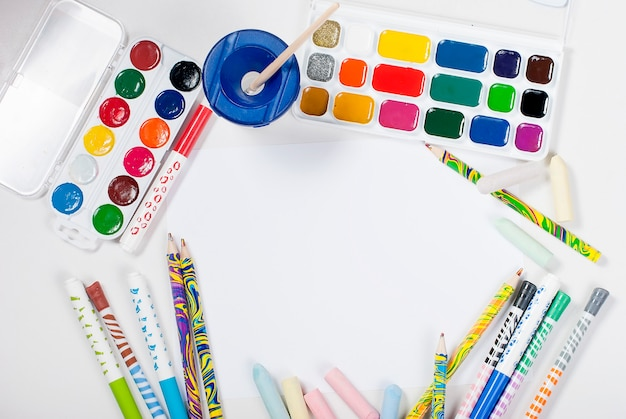 Waterverf en potloden op een witte achtergrond. bovenaanzicht. ruimte kopiëren.