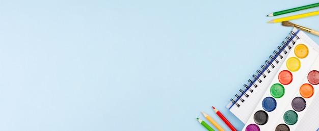 Waterverf met blocnote en potloden op een blauwe achtergrond.