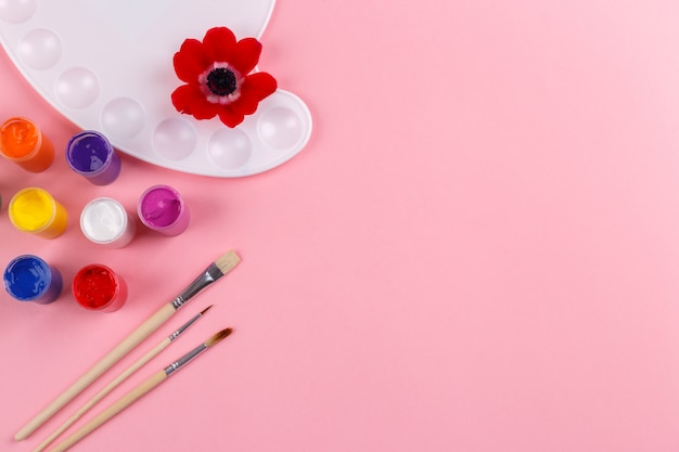 Waterverfpalet en borstels op roze achtergrond