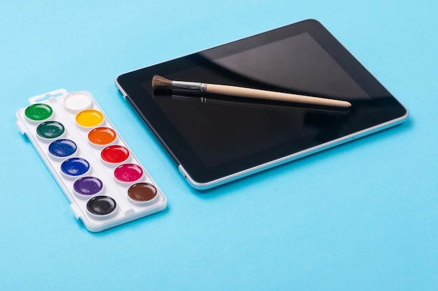 Waterverfverven en borstel die op tablet liggen die op blauw wordt geïsoleerd