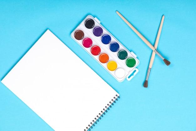 Waterverfverven en borstel met album voor schilderen geïsoleerd op blauw