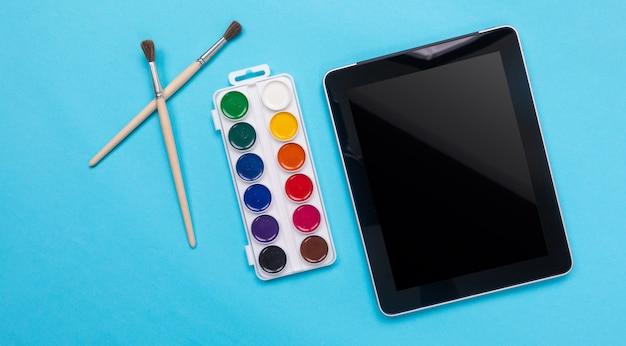 Waterverfverven en borstel met tablet op blauw