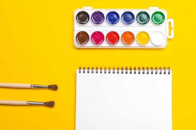 Waterverfverven en borstels met canvas voor het schilderen met copyspace op gele achtergrond