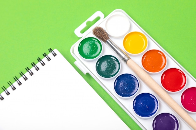 Waterverfverven en borstels met canvas voor het schilderen met copyspace op groen