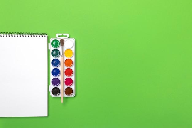 Waterverfverven en borstels met canvas voor het schilderen met copyspace op groene achtergrond