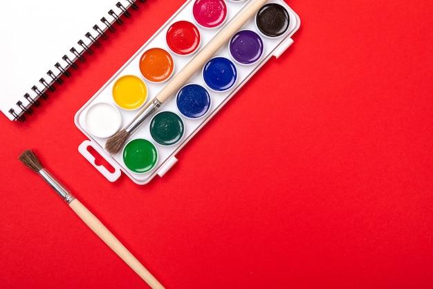 Waterverfverven en borstels met canvas voor het schilderen met copyspace op rood