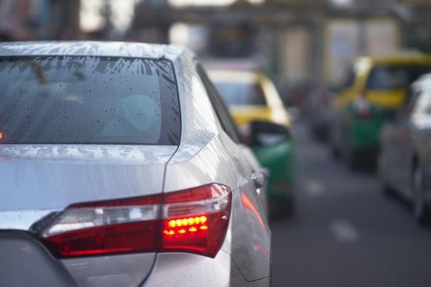 Watervorst en druppeltjes op achterwindschild van sedanauto op regenachtig seizoen op verkeer
