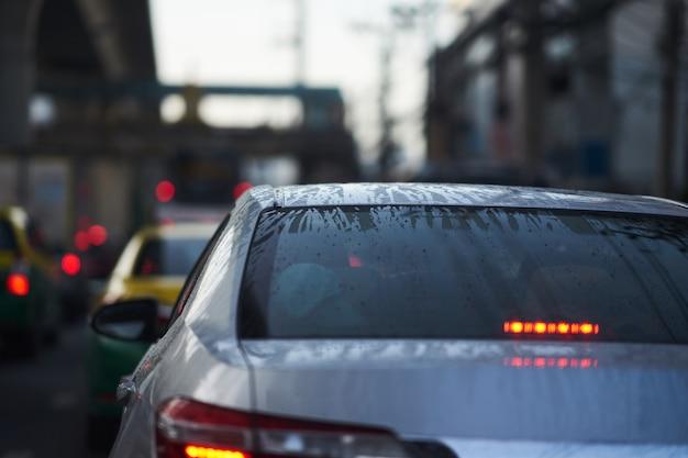 Watervorst en druppeltjes op achterwindschild van sedanauto op regenachtig seizoen
