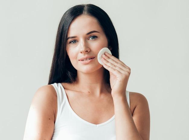 Wattenschijfje vrouw gezicht verwijderen make-up gezonde huid natuurlijke make-up. studio opname.