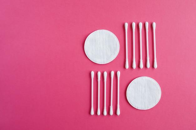 Wattenstaafjes en schijven geïsoleerd op een roze achtergrond. hygiëneproducten.