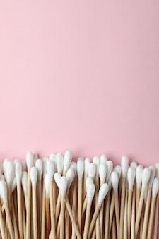 Wattenstaafjes op roze achtergrond, ruimte voor tekst