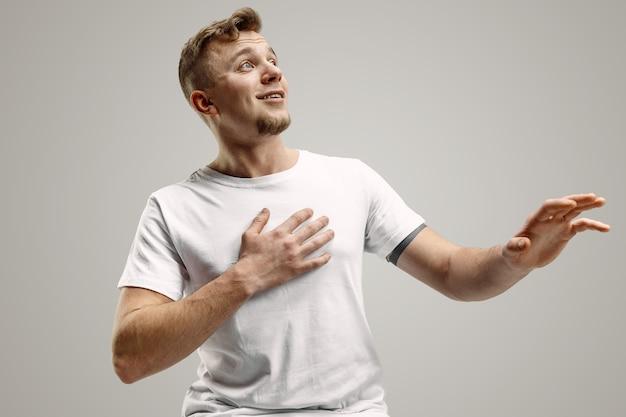 Wauw. aantrekkelijk mannelijk half-lengte voorportret op grijze achtergrondgeluid